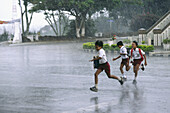 School children running out their school under a heavy monsoon rain, Bukittingi, Sumatra, Indonesia