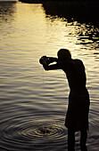 Sannyasin or saddhu offering water to the rising sun, in the Narmada river, Om Kareshwar, Madhya Pradesh, India