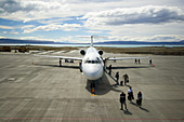 Passengers getting off at small airport to make a connecting flight in South  America