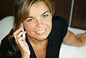 Young woman in her 30s speaking on a mobile phone, smiling, in an office in Cadiz, Spain  White sofa and wooden walls