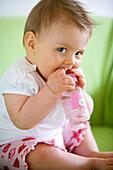 Baby girl (8 month) with a bottle, Vienna, Austria