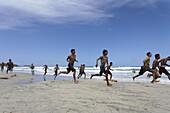 Young people running over sandy beach, Playa El Aqua, Isla Margarita, Nueva Esparta, Venezuela