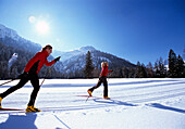 A couple cross-country skiing under blue sky, Tyrol, Austria, Europe