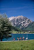 Family riding bikes at lake Achensee, Tyrol, Austria, Europe