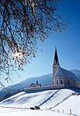 Church on a snow covered hill in the sunlight, Kreuth, Bavaria, Germany, Europe
