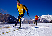 Two men cross-country skiing under blue sky, Tyrol, Austria, Europe