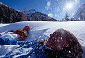 A couple lying in the snow laughing, Tyrol, Austria, Europe