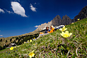Couple lying on an alpine meadow under blue sky, Dolomites, South Tyrol, Italy, Europe