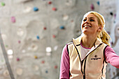 Young woman in front of a climbing wall in a hall, Bad Toelz, Bavaria, Germany, Europe
