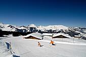 Skiers on a ski slope under blue sky, Kitzbuehel Alps, Tyrol, Austria, Europe