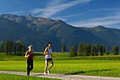 A couple running in an idyllic scenery, Tyrol, Austria, Europe