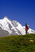 Woman with rucksack on a meadow in front of the Grossglockner, Hohe Tauern, Austria, Europe