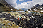 Woman with rucksack jumping over a mountain stream, Hohe Tauern, Austria, Europe