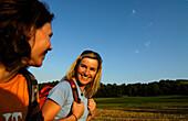 Two women hiking in the sunlight, Franconian Switzerland, Bavaria, Germany, Europe