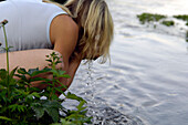 Woman washing her face at a stream, Bavaria, Germany, Europe
