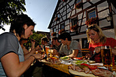 People eating at a beer garden in front of a half-timbered house, Franconian Switzerland, Bavaria, Germany, Europe