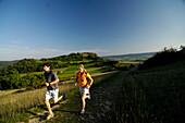Couple jogging in an idyllic landscape, Franconian Switzerland, Bavaria, Germany, Europe