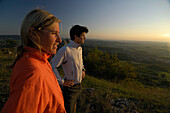 Joggers looking at the view at dusk, Franconian Switzerland, Bavaria, Germany, Europe
