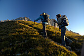 Two hikers at the ascent to Schuesselkar rock face, Tyrol, Austria, Europe