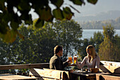 Young couple at a beer garden in the sunlight, lake Tegernsee, Bavaria, Germany, Europe