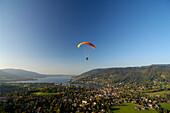 Person paragliding near Lake Tegernsee, near Rottach-Egern, Tegernsee, Upper Bavaria, Bavaria, Germany