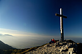 Couple on a hiking tour at heimgarten, having a rest at the summit cross, Upper Bavaria, Bavaria, Germany