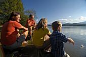 Family sitting on the shore of lake Staffelsee, near Murnau, Upper Bavaria, Bavaria, Germany