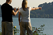Couple at Lake Tegernsee, Woman is pointing her finger towards something, Lake Tegernsee, Upper Bavaria, Bavaria, Germany
