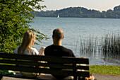 Couple having a rest on a bench near Lake Tegernsee, Upper Bavaria, Bavaria, Germany