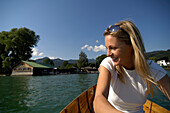 Woman rowing a boat in lake Tegernsee, Boat house in the background, Lake Tegernsee, Upper Bavaria, Bavaria, Germany