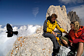 Couple having a rest at the mountain summit, Hiking tour in teh Rosengarten Mountain Range, Santnerpass, near Pozza di Fassa, Dolomites, South Tyrol, I5taly