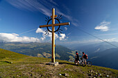 Two people on a mountain bike tour at the summit cross, Sattelberg, Brenner, Tyrol, Austria