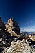 Two people hiking on gardena pass, near Wolkenstein, Dolomiten, South Tyrol, Italy