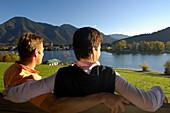 Couple sitting on a bench near Lake Tegernsee, Upper Bavaria, Bavaria, Germany, Europe