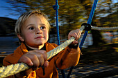 Child on the playground, Holding on to a climbing frame, near Tegernsee, Upper Bavaria, Bavaria, Hermany, Europe