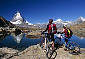Couple with mountain bikes enjoying view to Matterhorn, Zermatt, Canton of Valais, Switzerland