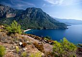 Mountain biker in front of Kabak Beach in a bay, Lycian coast, Turkey, Europe