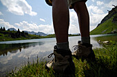 View at the legs of a hiker in front of a mountain lake, Allgaeu Alps, Bavaria, Germany, Europe