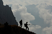 Hikers with hiking poles in front of overcast mountains, Rosengarten, Dolomites, South Tyrol, Italy, Europe