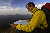 Hiker reading map, Klammspitze, Bavaria, Germany