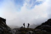 Hikers with rucksack in front of overcast mountains, Wetterstein, Bavaria, Germany, Europe