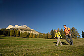 Young couple hiking under blue sky, Rosengarten, Dolomites, South Tyrol, Italy, Europe