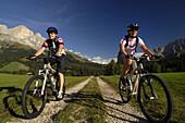 Two mountain bikers on dirt road, Rosengarten, Trentino-Alto Adige/Südtirol, Italy