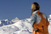 Frau betrachtet verschneite Bergkulisse, Fügen, Zillertal, Tirol, Österreich