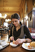 Mid adult woman having breakfast in a cafe, Vienna, Austria