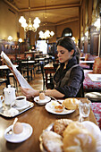 Mid adult woman reading newspaper while having breakfast in a cafe, Vienna, Austria