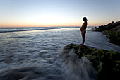 Pregnant woman standing on a rock on the beach at sunset, Conejo beach, Baja California Sur, Mexico