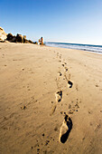 Footprints on the beach with a pregnant women in the background putting her towel down, Conejo beach, Baja California Sur, Mexico