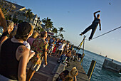 Acrobat performs on high wire with crowd watching.