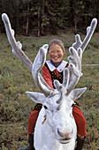 Tsaatan girl riding a reindeer. Red taiga. Khovsgol province. Mongolia